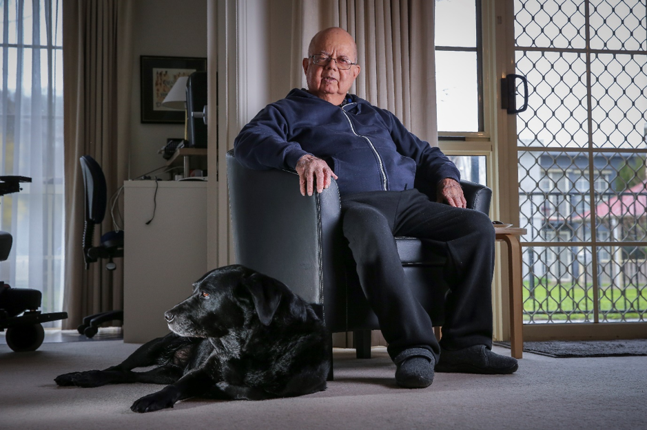 Twanny Farrugia sitting in a chair at home with his guide dog and companion Val.