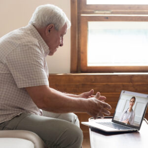 An older patient talking to their GP using a laptop.