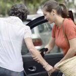 A young carer holding the hand of an older person to help them into a car.