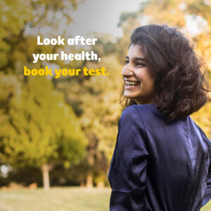 """Image of a smiling woman with the text """"Look after your health, book your test."""""""