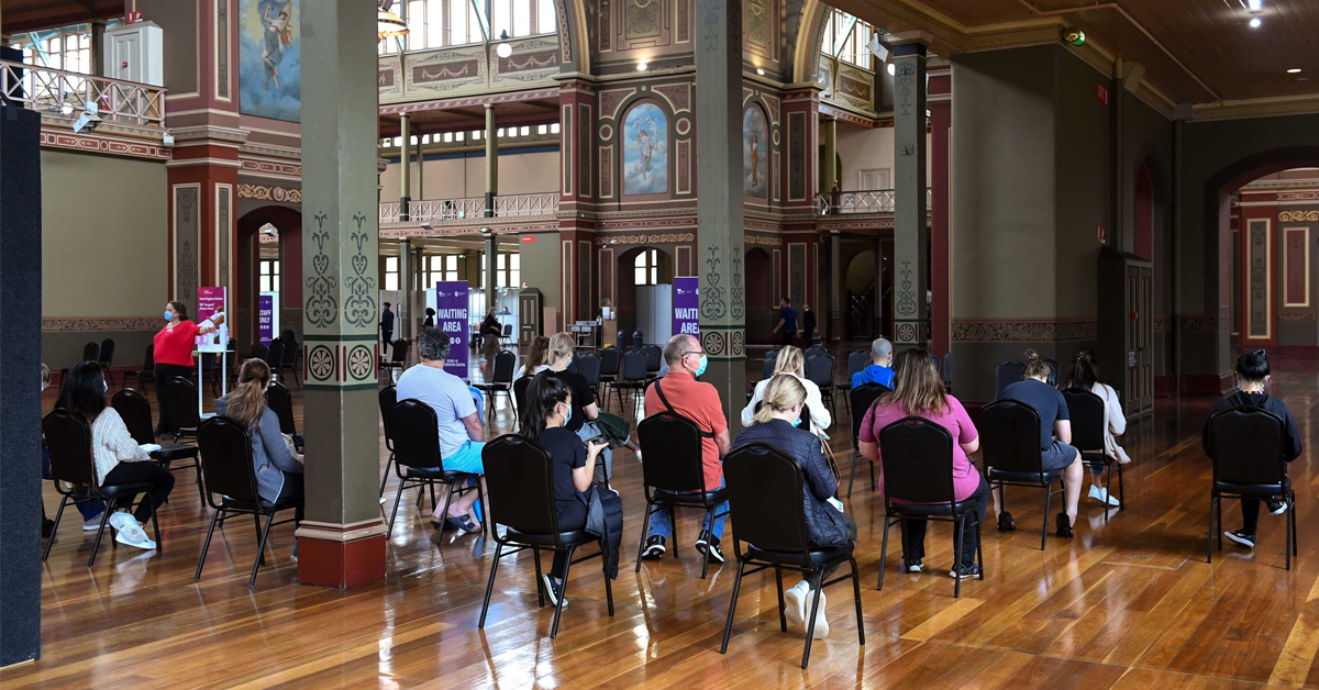 People waiting to receive their COVID-19 vaccine at the Royal Exhibition Building in Carlton.