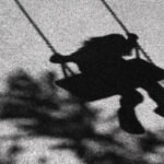 Shadow of a young child on a playground swing.