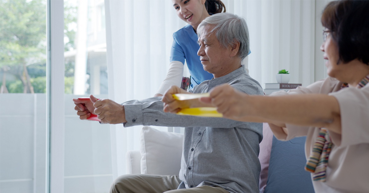 Two older people living in aged care doing strengthening exercises with an allied health practitioner.