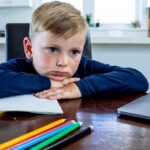 A child looking unhappy while home schooling.