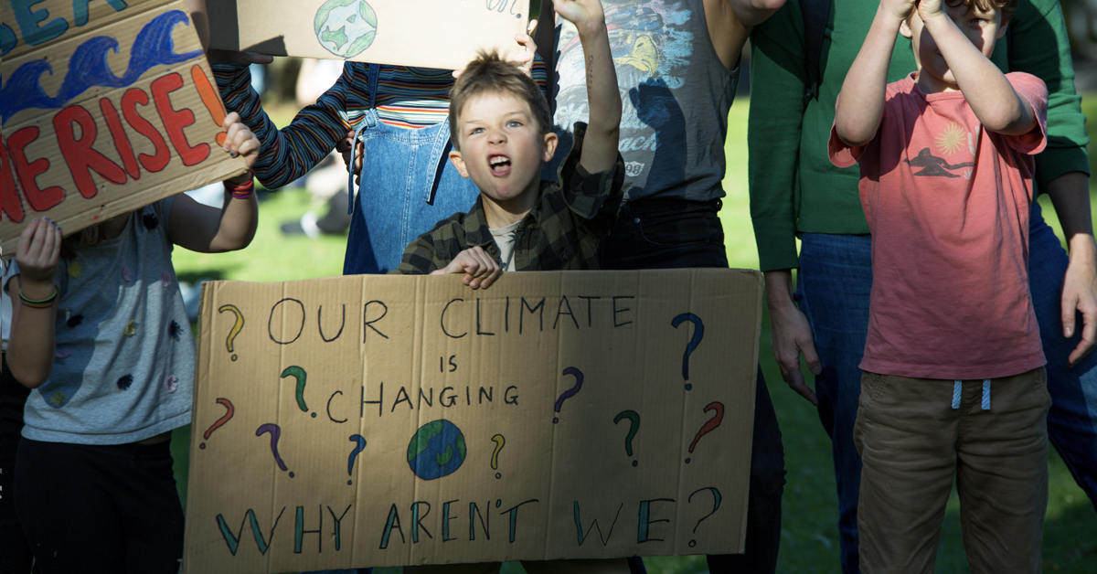 """A young person at a climate change protest in Melbourne with a sign that reads """"Our climate is changing, why aren't we?"""""""